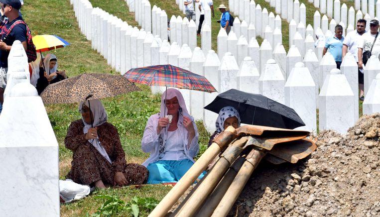 Bosnische moslimvrouwen en familie van de slachtoffers van Srebrenica wachten op de begraafplaats bij het stadje Potocari op de begrafenis van lichaamsdelen van mensen die in 1995 zijn vermoord.    Beeld AFP