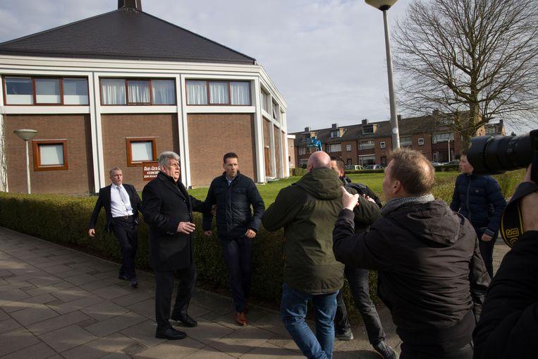 De man in spijkerbroek en groene jas is een beveiliger van de NOS (ook aanwezig om verslag te doen) die ingrijpt nadat een journalist van RTV Rijnmond is aangevallen bij een gereformeerde kerk in Krimpen aan de IJssel. Beeld Arie Kievit