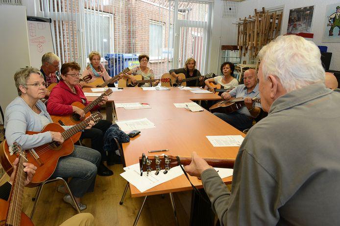 """Archieffoto (2014): Met z'n allen tokkelen op de gitaar. """"Welke snaren gebruik jij en hoe moet ik mijn vingers neerzetten?"""" Het is slechts een van de activiteiten van het Senioren Hobby Centrum in Mill."""