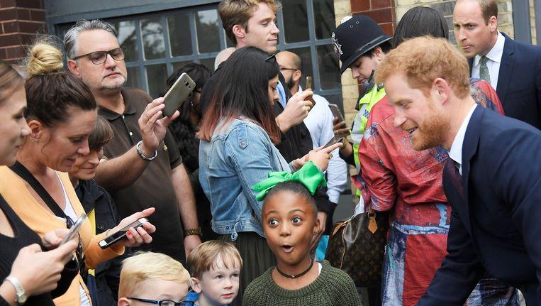 Een meisje reageert op haar ontmoeting met Prins Harry die samen met zijn broer (rechts achterin) de steungroep Support4Grenfell bezoekt.