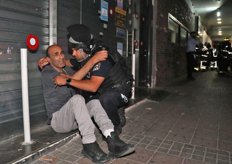 Een lid van de Israëlische veiligheidstroepen probeert een man te kalmeren in de stad Holon, nabij Tel Aviv, nadat vanuit de Gazastrook raketten werden afgevuurd. Beeld AFP