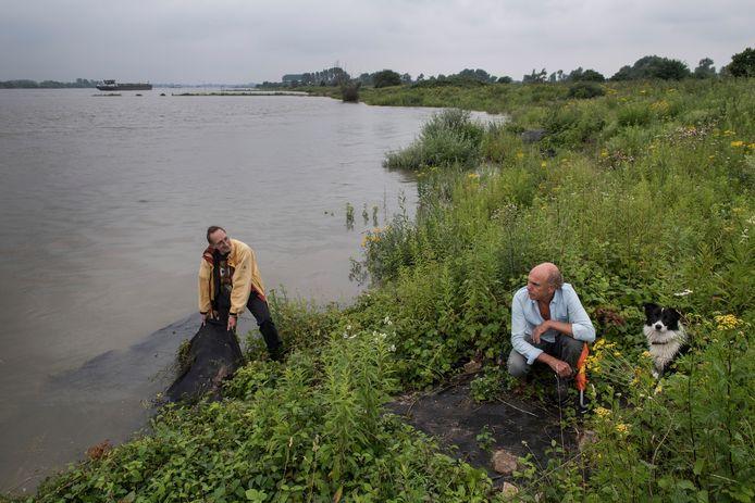 Kasper Heineke (r) en Ewout in de uiterwaarden langs rivier De Waal bij worteldoek dat door stroming en golfslag aan het loslaten is - het worteldoek is ooit uitgevonden door de vader van Ewout.