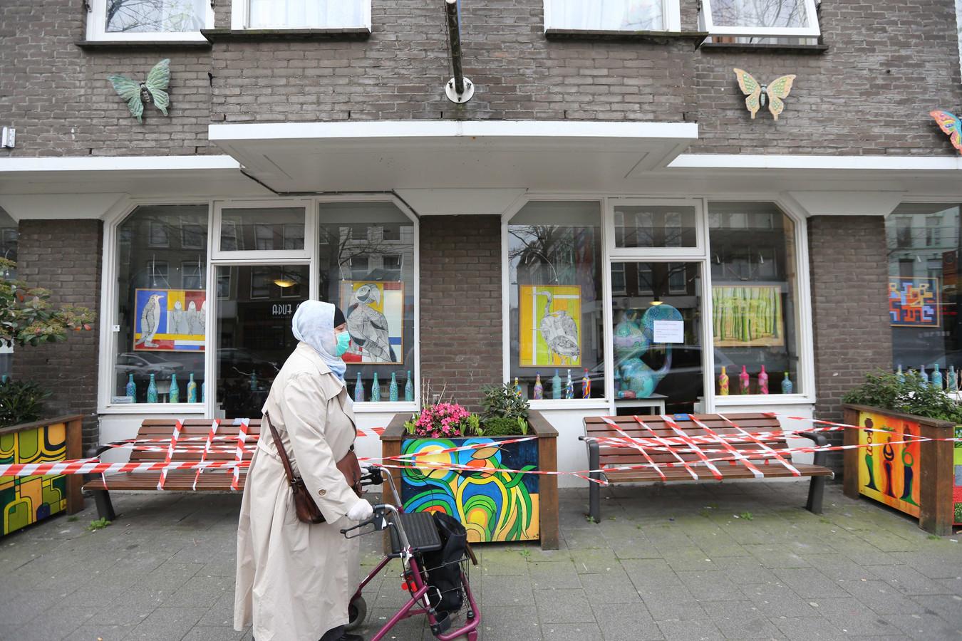 Bankjes voor het Rotterdamse verpleeghuis De Leeuwenhoek zijn gesloten met lint. Bijna de helft van de bewoners van een afdeling voor dementerende ouderen is de afgelopen drie weken overleden, vermoedelijk allemaal aan corona.