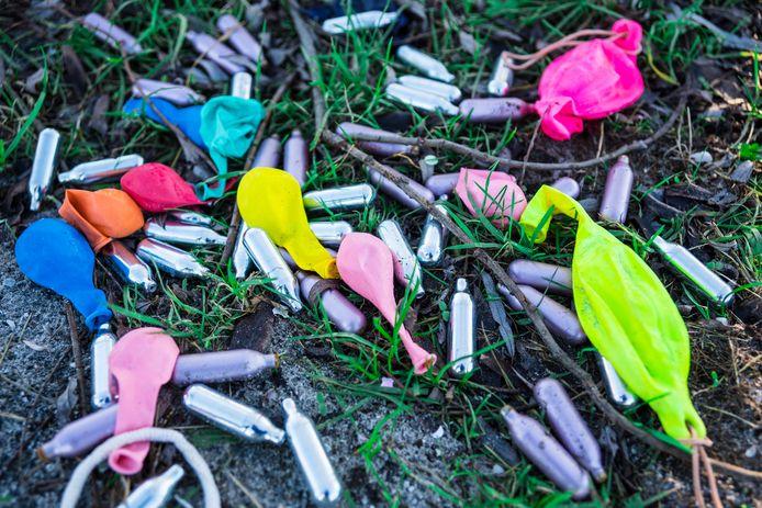 Patronen lachgas met ballonnen. Het gebruik van lachgas als harddrug kan blijvende schade aan de gezondheid aanrichten.