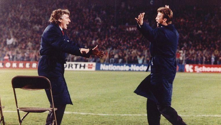 Louis van Gaal loopt juichend af op hulptrainer Gerard van der Lem nadat Ajax met 3- van Gent heeft gewonnen. Beeld ANP