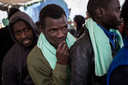 Migranten in de rij om één voor één van boord te gaan.