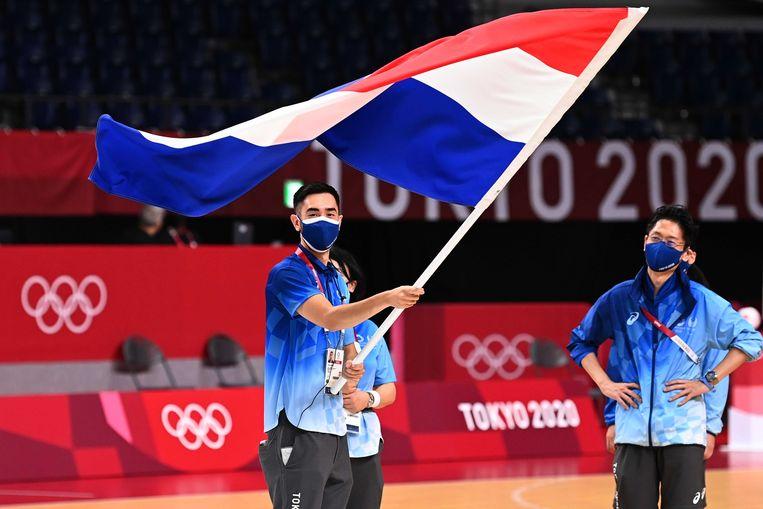 Japanse medewerkers van de olympische organisatie oefenen met de Nederlandse vlag voor de openingsceremonie tijdens de training van het vrouwenhandbalteam in de Yoyogi-sporthal in Tokio. Oranje begint op de Olympische Spelen met een wedstrijd tegen gastland Japan.  Beeld ANP