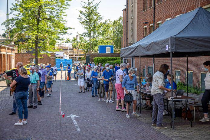 Lange rijen gistermiddag in Zwolle waar mensen hun coronavaccinatie lieten registreren in het gele boekje.