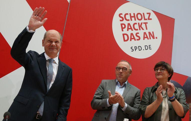 SPD-leider Olaf Scholz (l.) arriveert bij een bijeenkomst van zijn partij, een dag na de verkiezingen.  Beeld Wolfgang Kumm/dpa