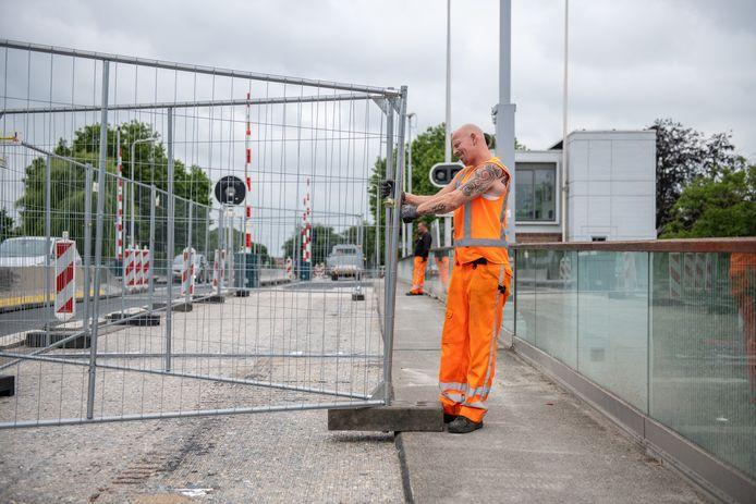 Medewerkers van verkeersbedrijf Versluys plaatsen hekken op de Julianabrug. Op de voorgrond het gefreesde deel. Daaronder bleken scheuren in de constructie van de brug te zitten.