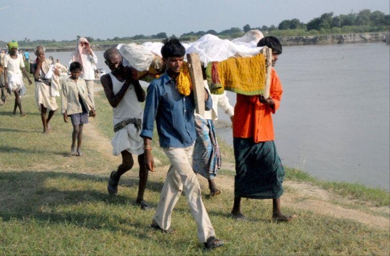 Indiase bewoners dragen het lichaam van een slachtoffer van het bootongeluk. (AFP) Beeld AFP