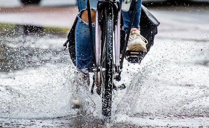 Lekker op de fiets door de plassen razen. Leuk, maar de steeds heviger plensbuien zorgen ook voor schade.