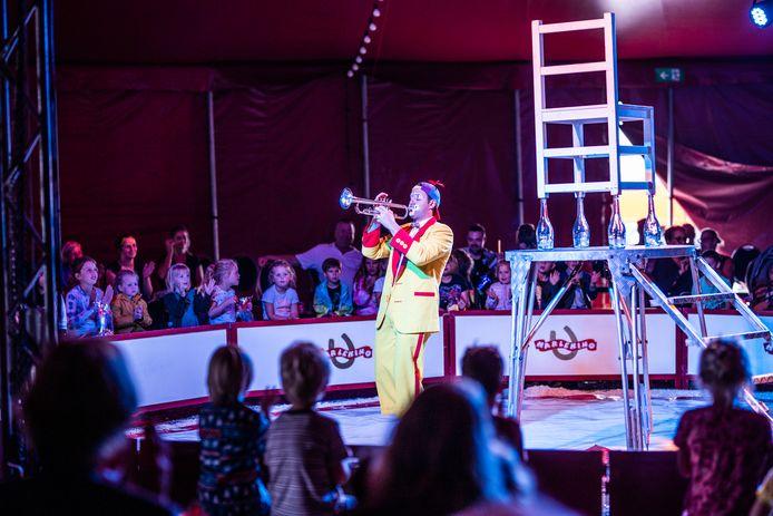Een clown trompettert in de tent van circus Harlekino in Arnhem.