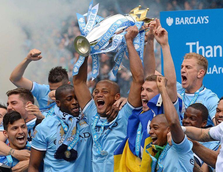 Manchester City viert de Engelse titel. De Belgische aanvoerder Vincent Kompany tilt als eerste de beker omhoog. Beeld afp
