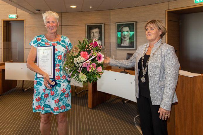 Ineke Niemantsverdriet krijgt van burgemeester Marleen Sijbers een penning, een oorkonde en bloemen voor haar bijzondere reddingsactie.