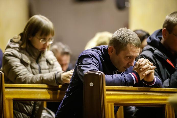 Poolse kerkgangers verzonken in gebed tijdens de dienst in de rooms-katholieke kerk in Nieuw-Vossemeer.