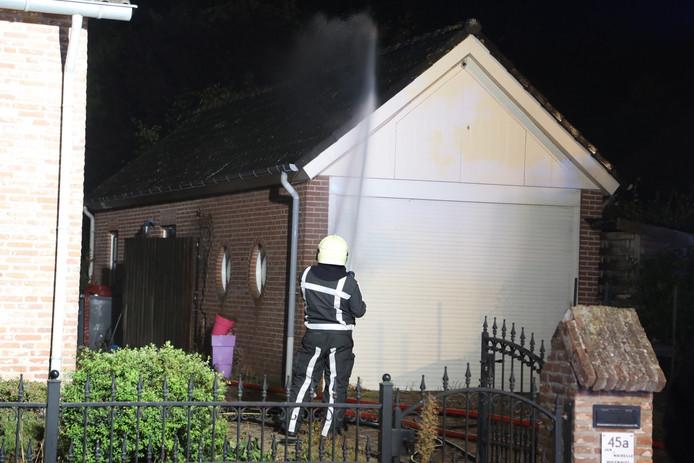 Een naastgelegen gebouw wordt natgehouden om overslaan van het vuur te voorkomen.