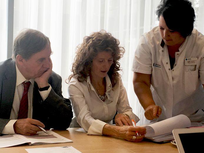 Prof. Robert Mansel en Lorenza Marotti buigen zich over de dossiers die verpleegkundig specialist Saskia Claassen hen aanreikt.