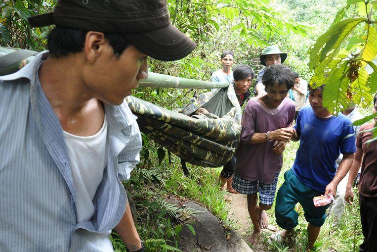 Ho Van Lang (midden, in het paarse shirt) en zijn vader (liggend in de draagbaar) worden in 2013 uit de jungle gehaald. Beeld EPA