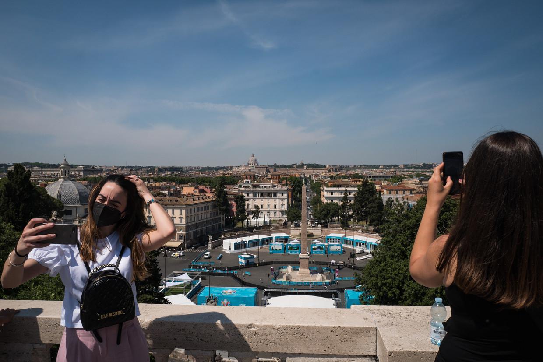 Vrouwen maken selfies op een heuvel die uitkijkt over het Piazza del Popolo, waar het Football Village wordt aangelegd. Beeld Nicola Zolin
