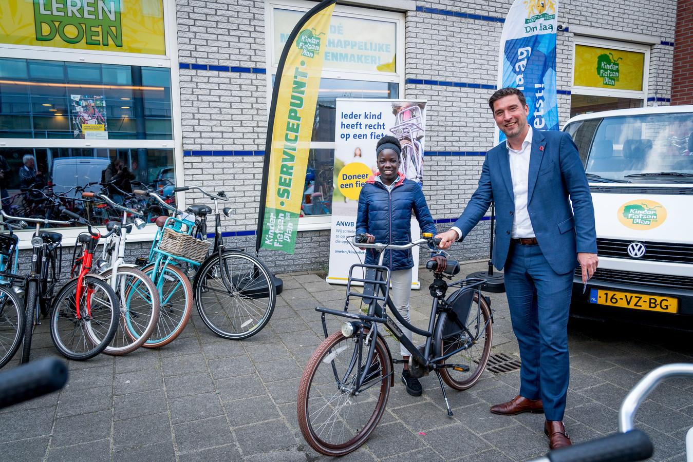 Wethouder Robert van Asten (Mobiliteit) geeft de eerste Haagse fiets uit dit plan aan Laura.