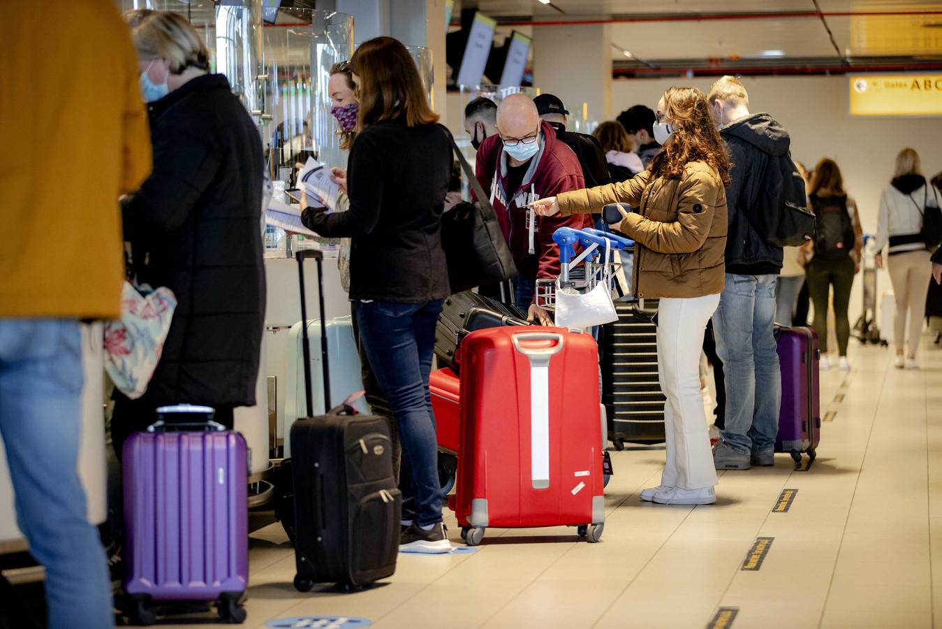 Reizigers checken in op Schiphol.