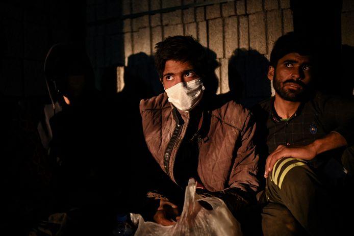 Afghaanse migranten wachten op transport dat wordt aangeboden door mensensmokkelaars aan de Iraans-Turkse grens.
