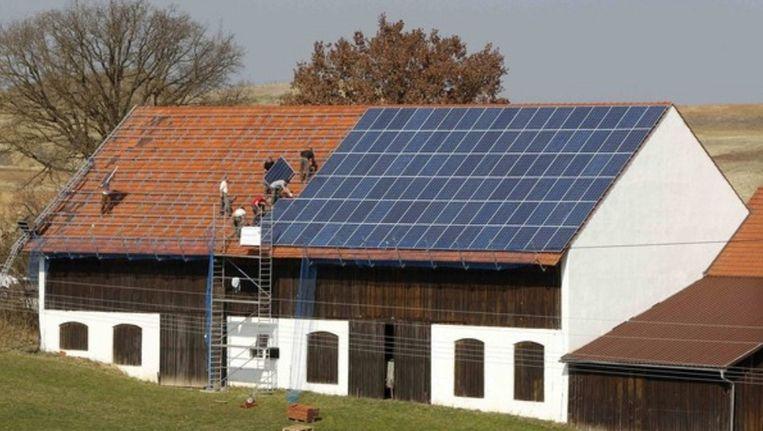 Het dak van een Duitse boerderij wordt volgelegd met zonnepanelen. Ook als het Chinese panelen zouden zijn, verdient Duitsland hier zelf verreweg het meeste aan. Beeld Reuters