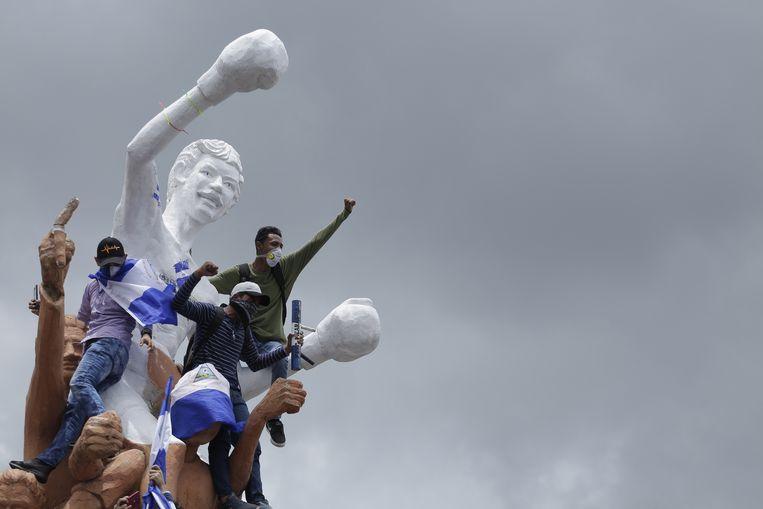 Demonstranten beklimmen het standbeeld van bokser Alexis Arguello tijdens een protestmars tegen president Ortega. Beeld EPA