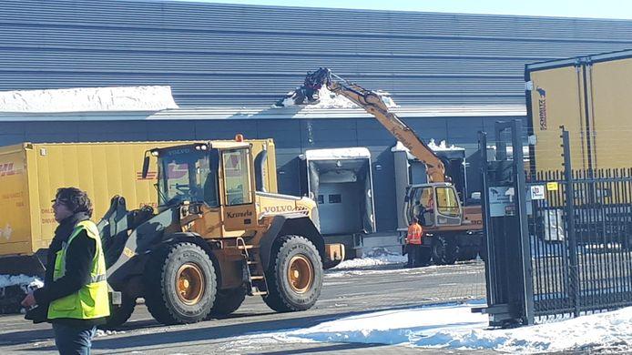 Bij DHL in Duiven wordt het dak sneeuwvrij gemaakt nadat het misging bij de buren van TNT.