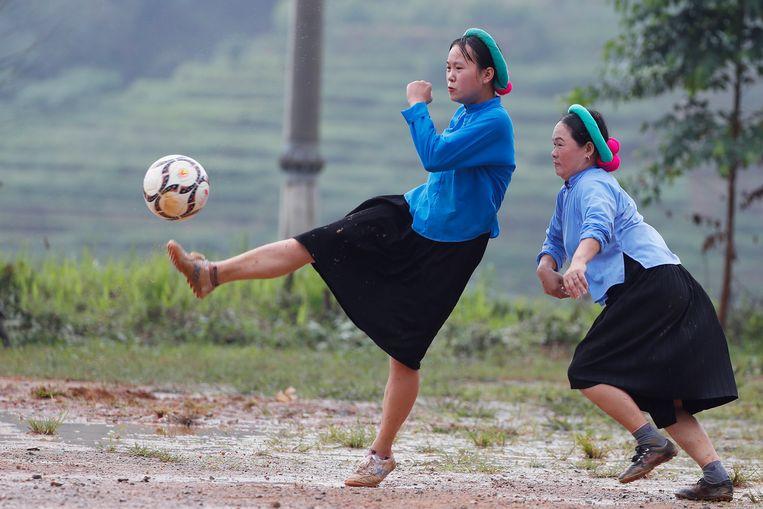 Jonge Vietnamese vrouwen in traditionele kledij spelen een potje voetbal in Huc Dong,  in het noordoosten van het land.  Beeld EPA