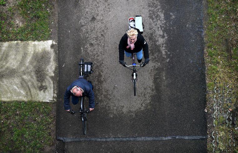 Een gewone fiets en een e-bike op de Waaldijk bij Wamel.  Beeld Marcel van den Bergh
