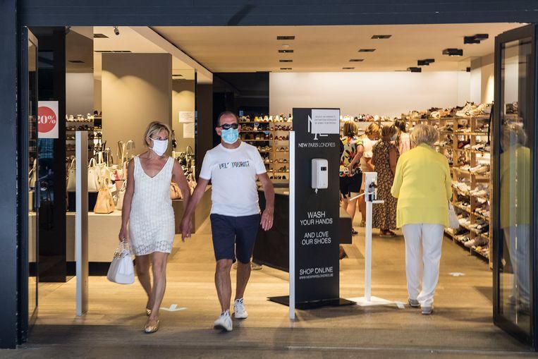 Een koppel loopt met mondkapje op een winkel uit in Sluis. Beeld Arie Kievit