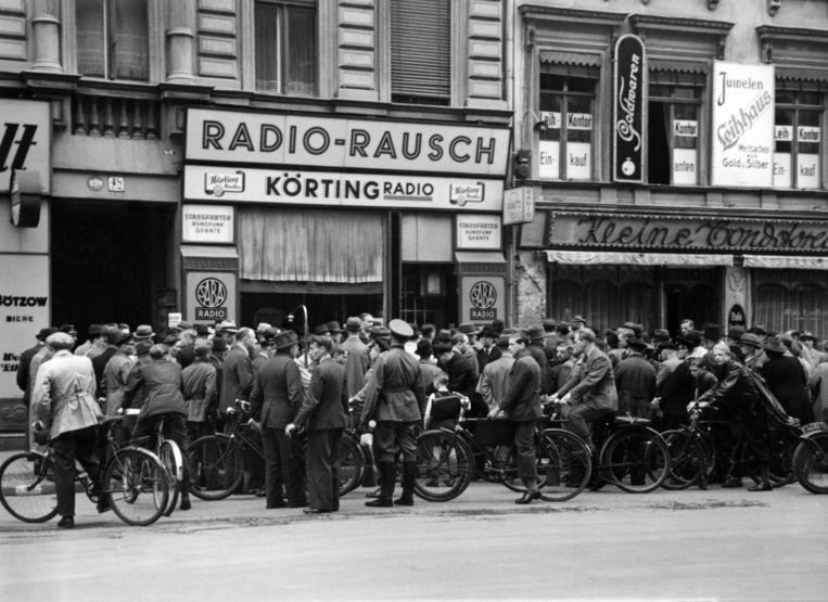 Berlijn 1940: mensen troepen samen voor een radiowinkel, benieuwd naar het dagelijkse militaire verslag van de nazi's. Beeld BELGAIMAGE