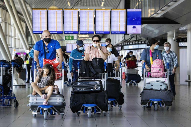 Reizigers op luchthaven Schiphol. Net nu voor velen de zomervakantie is begonnen, heeft Nederland vanwege de toename van het aantal coronabesmettingen kleurcode rood op de Europese coronakaart. Beeld ANP