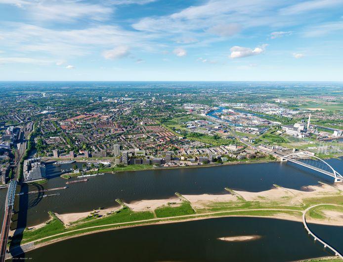 Het Waalfront zoals dat er uit komt te zien. Een strook met meer dan duizend woningen tussen spoorbrug (links) en die andere Waalbrug, De Oversteek (rechts).