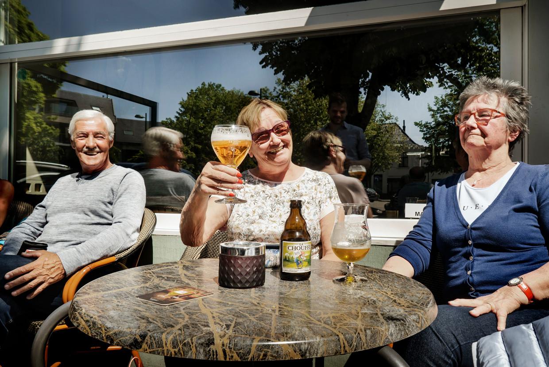Marie-Jeanne (72), met zonnebril, kan nog genieten op een terras in Evergem. Beeld Eric de Mildt