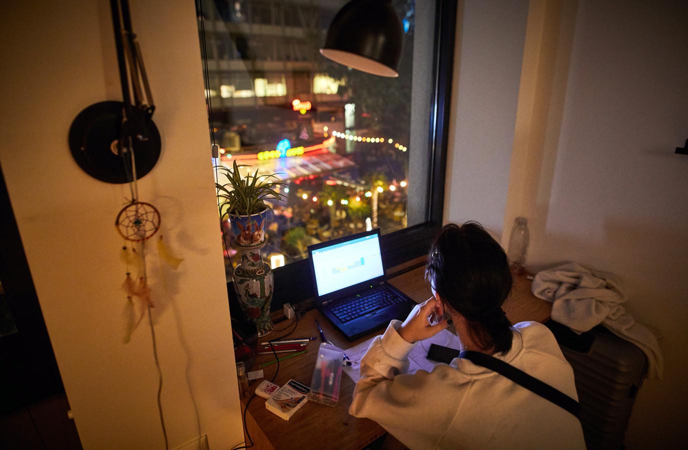Een studente werkt in haar kamer vlakbij de terrassen aan het Stadhuisplein.