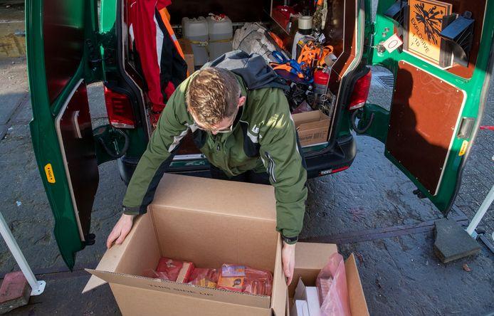 Een medewerker van een gespecialiseerd bedrijf laadt het ingezamelde vuurwerk in.
