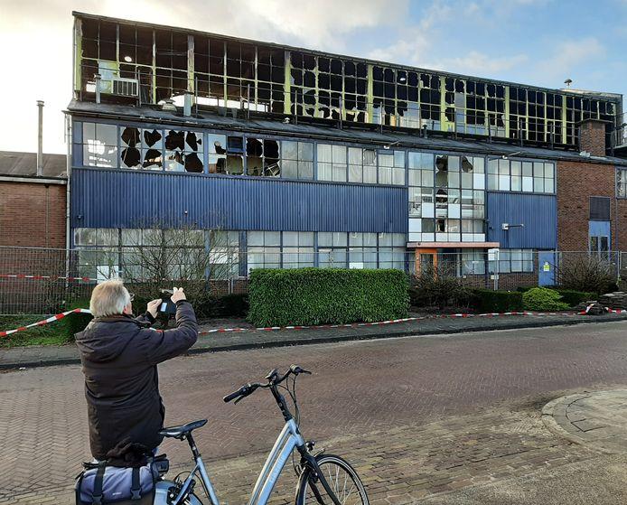 Iemand maakt een foto van het door brand verwoeste pand aan de Eerbeekse Enkweg. Hij is deze maandag bepaald niet de enige.