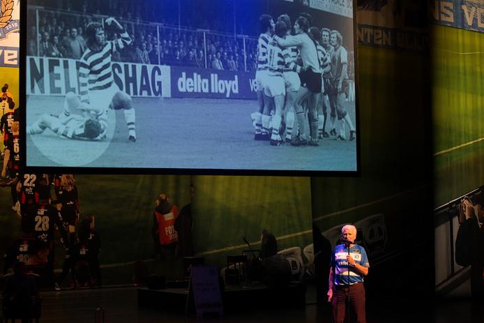 Henk Overgoor met achter hem de foto van de wedstrijd De Graafschap -Feijenoord waarop Guus Hiddink hem verlost van het ingeslikte gebit. Een van de verhalen uit Veur Altied...