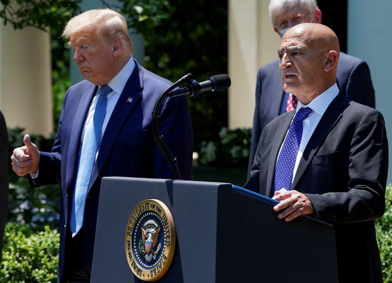 Moncef Slaoui, in mei aangesteld als hoofd van 'Operatie Warp Speed', doet in de rozentuin van het Witte Huis zijn vaccinbeleid uit de doeken. President Trump hoort dat het goed is. Beeld REUTERS