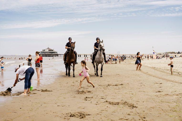 Politie te paard patrouilleert tussen de zwemmers in Blankenberge. Beeld Eric de Mildt