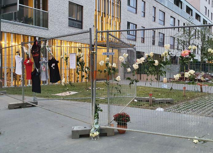 Aan de hekken aan de Jan Vanhoenackerstraat hangen bloemen, teksten en voetbalshirts.