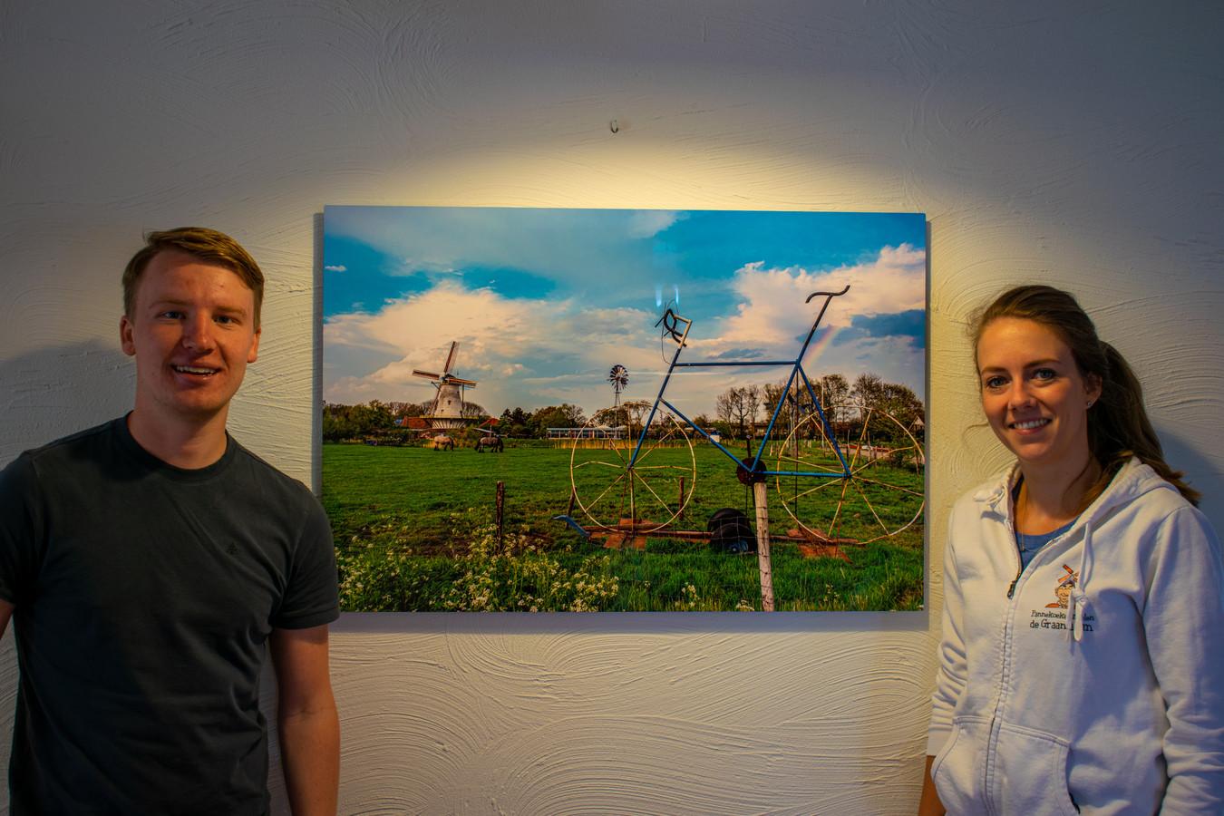 Rick den Biggelaar voor een van zijn afgedrukte foto's met Kiki Meijer van de pannenkoekenmolen de Graanhalm waar de platen de hele zomer hangen.