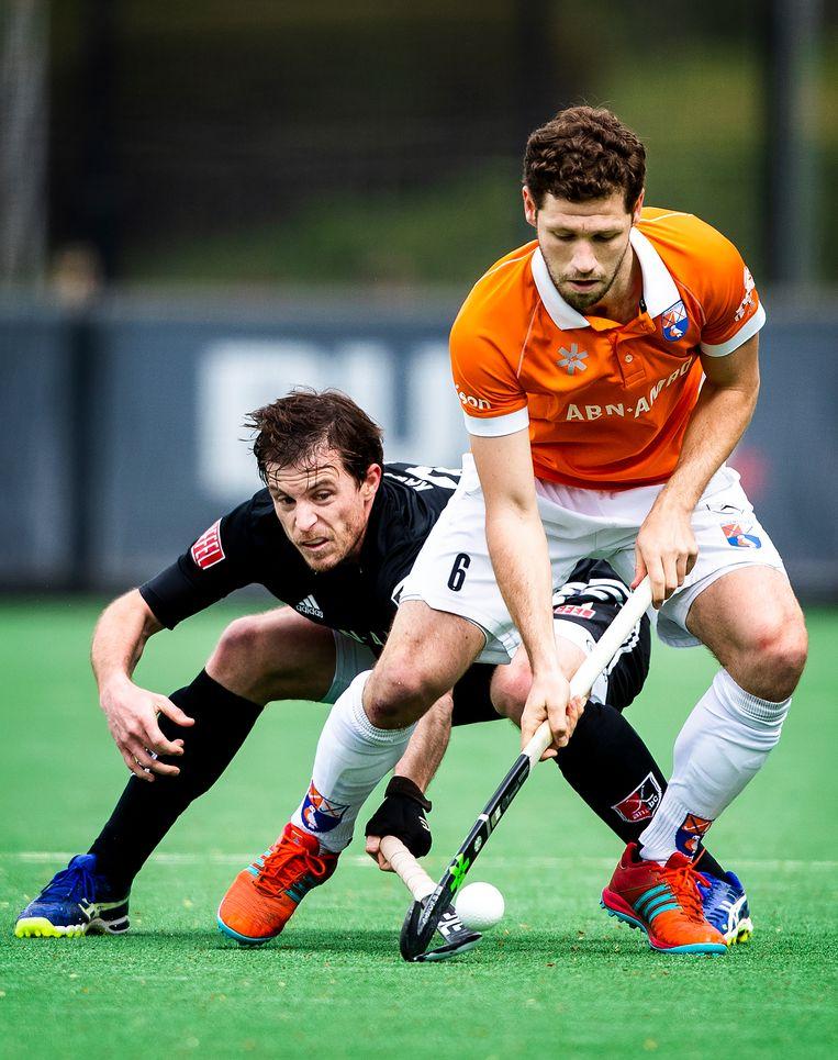Sander 't Hart van Bloemendaal (in oranje) wint een duel van Amsterdam-speler Fergus Kavanagh. Beeld Jiri Büller / de Volkskrant