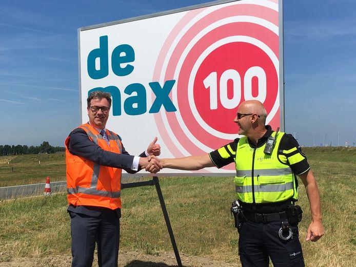 Gedeputeerde Harry van der Maas (l) onthult samen met Dries Zoutewelle van de Verkeerspolitie langs de Sloeweg het bord 'De max is 100'.