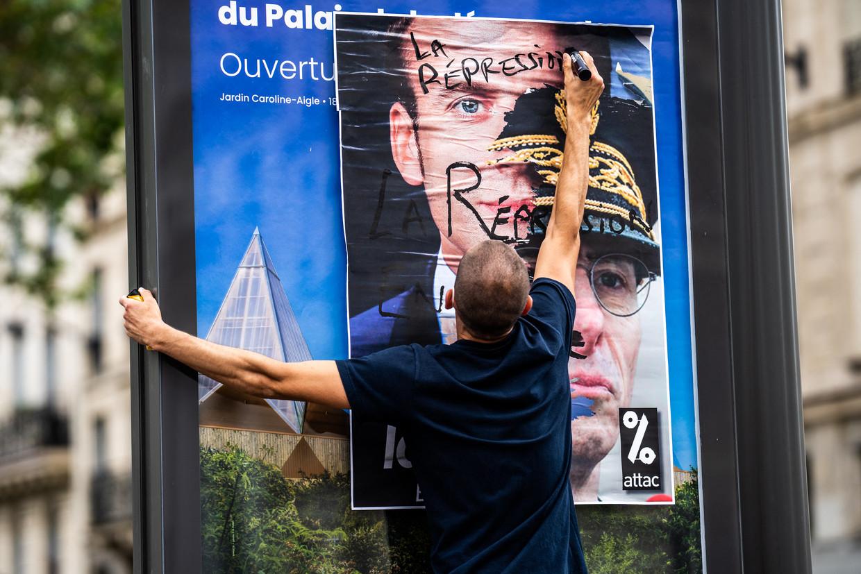 Een man bekladt het hoofd van Macron. Repressie! Beeld Hans Lucas via AFP