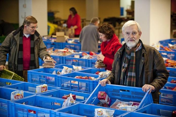 Mensen van de Voedselbank pakken de pakketten in. Met de Almelose secretaris Marinus Trommel op de voorgrond. Foto Emiel Muijderman