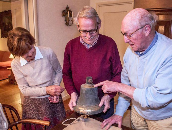 Hans en Ria van Poppel buigen zich met Ben Robben (midden) over de bel die een Schotse bevrijder op 27 oktober 1944 aan de Tilburger Louis van Riel heeft gegeven.